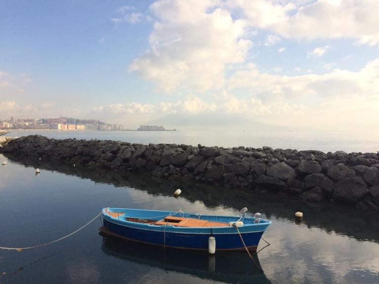 A local boat in the Porto di Napoli, with the active volcano Mount Vesuvias visible in the background.